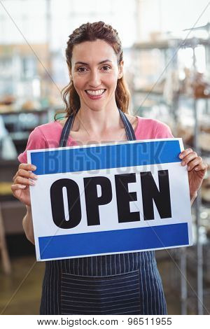 Pretty worker showing open sign at the bakery
