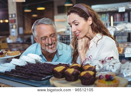 Cute couple looking at cakes in the bakery store