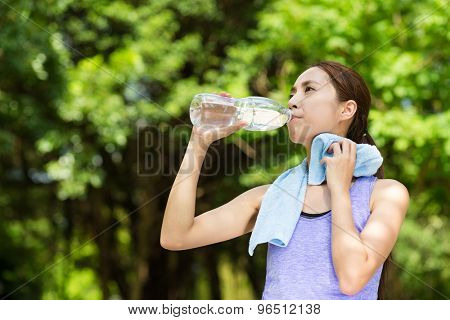 Beautiful young asian woman drinking water after training