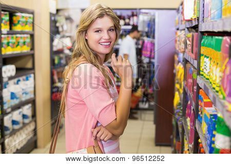 Portrait of a smiling young woman buying a products in supermarket