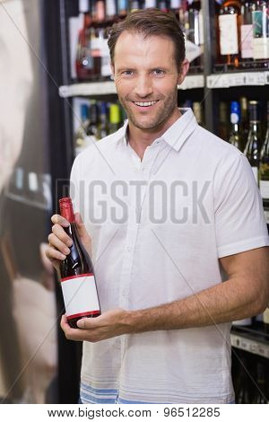 Portrait of a smiling handsome showing a wine bottle in supermarket