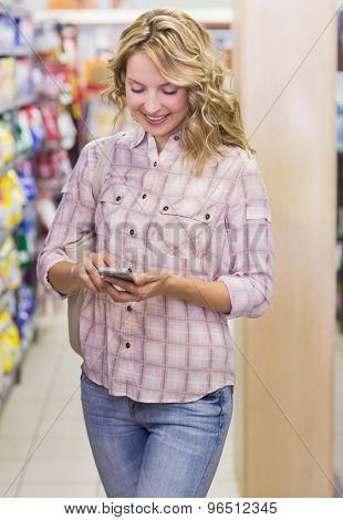 Smiling pretty blonde woman using her smartphone in supermarket