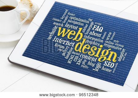 web design word cloud with binary background on a digital tablet with a cup of coffee