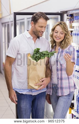 Smiling casual couple looking at water bottle in supermarket