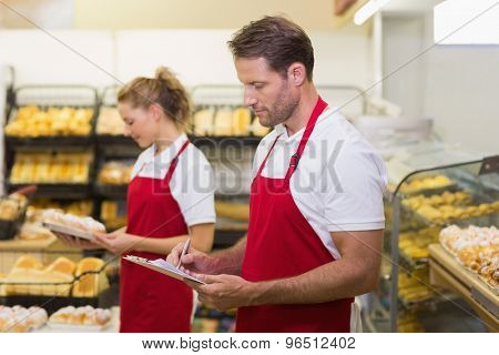 Side view of two bakers writing on a notepad in bakery