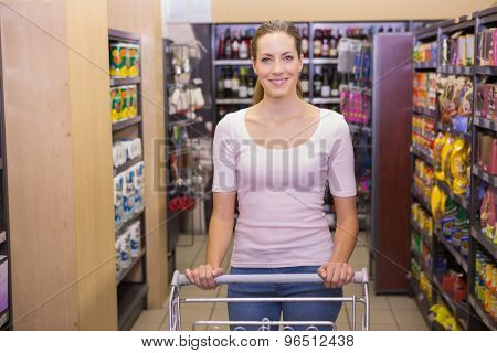 Pretty woman looking at camera and pushing trolley in supermarket