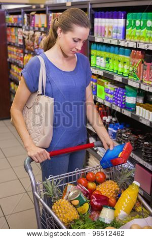 Pretty woman putting product in trolley at supermarket
