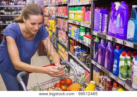 Pretty woman pushing trolley in aisle and texting at supermarket