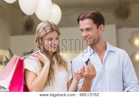 A happy couple looking at beauty product at the mall