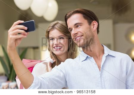 A couple taking a selfie at the mall