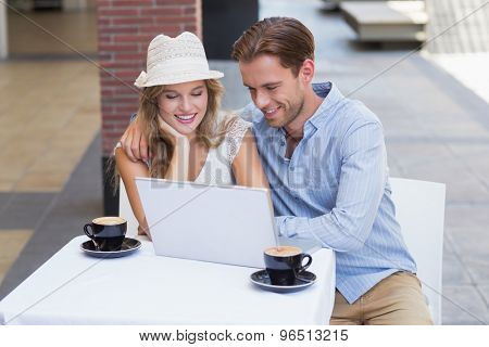 Cute couple looking at a laptop at the cafe terrace