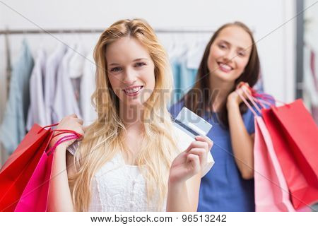 Portrait of a happy friends holding a credit card