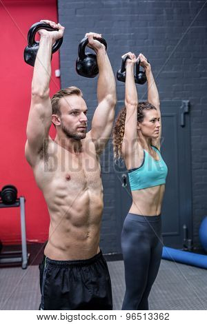 Side view a muscular couple lifting kettlebells