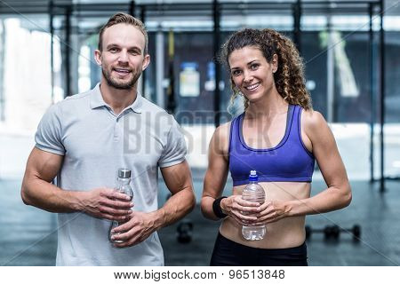 Portrait of a muscular woman with her trainer