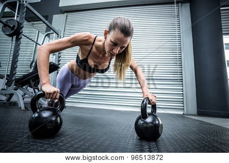 Front view of a woman doing pushups with kettlebells