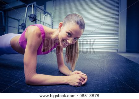 Portrait of a muscular woman on a plank position
