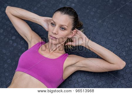 Upward view of a muscular woman doing abdominal crunch