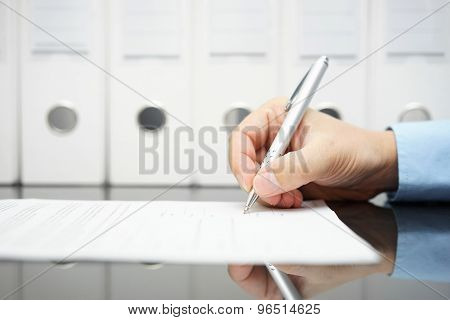 Businessman Is Signing Contract With Binders In Background