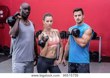 Portrait of serious muscular athletes lifting kettlebells