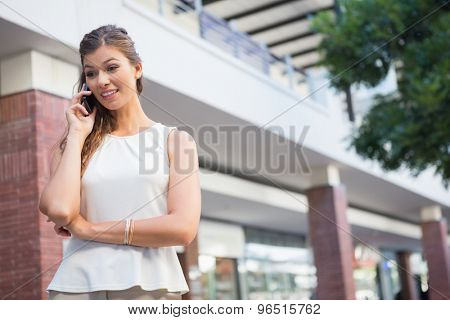 Smiling woman calling with smartphone at the shopping mall