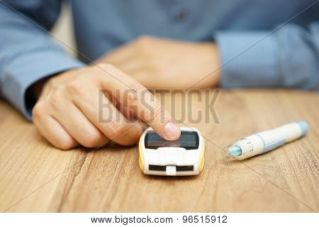 Man Testing Glucose Level With A Digital Glucometer, Diabetes Treatment