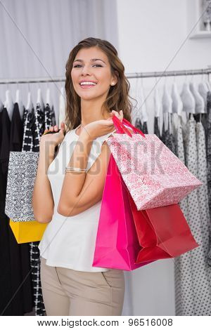 Portrait of smiling woman with shopping bags looking at camera at a boutique