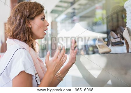 Astonished woman touching window with one hand at the shopping mall