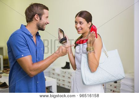 Young couple deciding on which shoe to choose in the shoe store