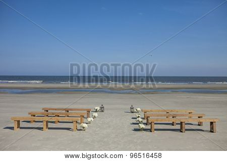 Beach wedding venue with benches and flowers