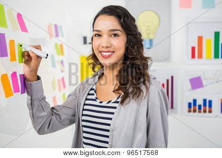 Young smiling creative businesswoman in the office writing on sticky notes