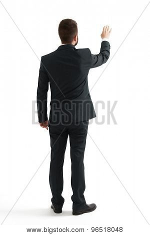 back view of businessman in formal wear raising up his hand like pushing screen. isolated on white background