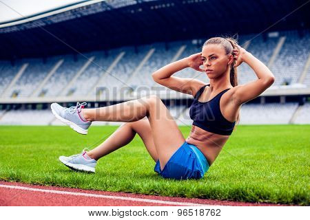 Fitness woman on stadium doing abdominal exercise