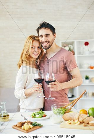 Amorous man and woman toasting with red wine in the kitchen