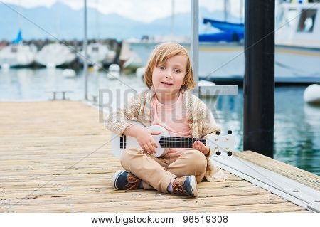 Little happy boy plays his guitar or ukulele, resting by the lake