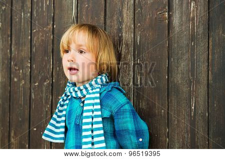Fashion portrait of a cute little blond boy against wooden background, wearing emerald shirt and sca