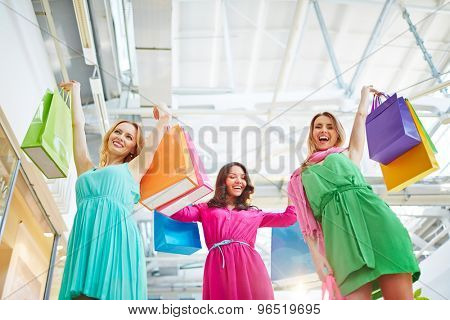 Joyful shopaholics holding paperbags in raised hands