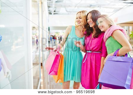 Charming shoppers discussing lingerie in the shop window