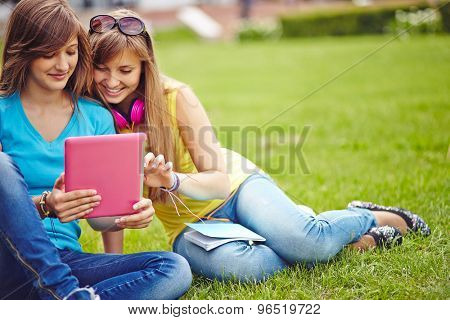 Friendly girls with touchpad networking on green lawn