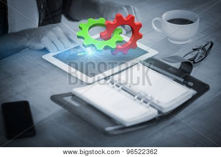 Green and red cog and wheel against creative businessman using a tablet