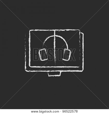 Headphone in screen monitor hand drawn in chalk on a blackboard vector white icon on a black background