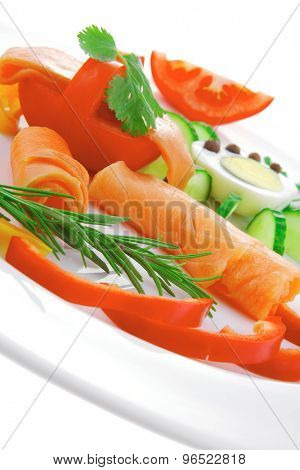 diet healthy food - smoked sea salmon rolls with vegetables and egg on plate isolated over white background