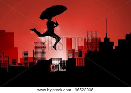 Woman jumping with umbrella against cityscape stencil on red