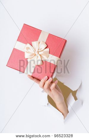 Hand break through paper with red gift box