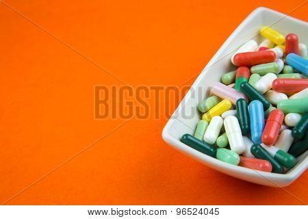 Lots Of Pills On Orange Background