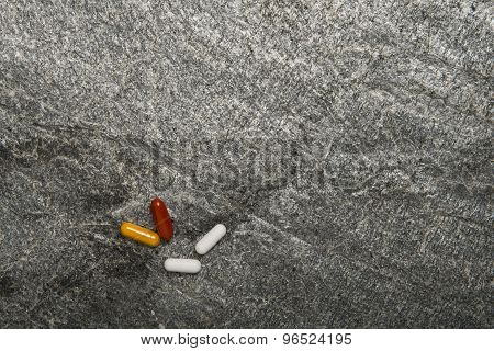 Herbal pills on stone background