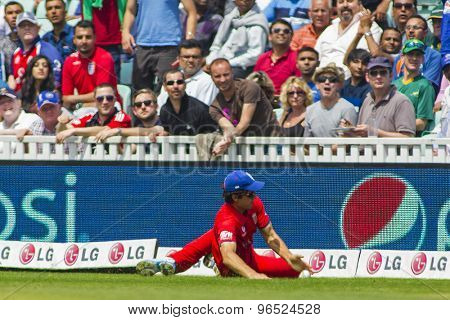 LONDON, ENGLAND - June 19 2013: England's captain Alastair Cook saves a boundary during the ICC Champions Trophy semi final match between England and South Africa at The Oval Cricket Ground