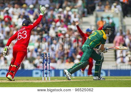 LONDON, ENGLAND - June 19 2013: England's Jos Buttler catches the ball to dismiss Chris Morris during the ICC Champions Trophy semi final between England and South Africa at The Oval Cricket Ground