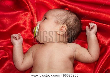 Newborn Baby Lying On Red Silk