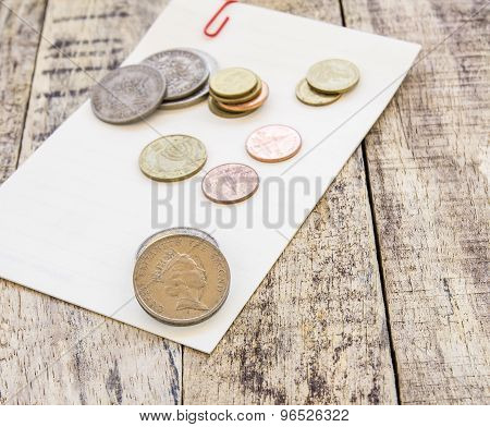 Coin On White Paper On Wooden Table