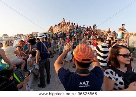 Oia,Santorini, GREECE - June 14, 2015:A CROWD OF TOURISTS AWAITS THE FAMOUS SANTORINI SUNSET